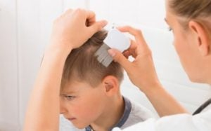 Mom using lice comb to remove hair from boys head