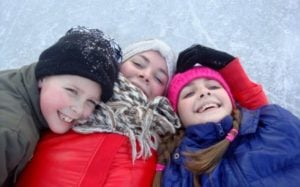 3 kids dressed in snow suits in the winter laying on skating rink