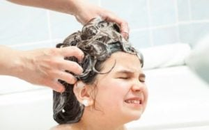 4 year old girl getting her hair washed with soap in the bath tub